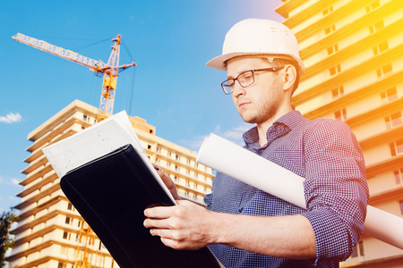 storey: Close-up of a male construction worker wearing a helmet, glasses, a shirt in his hands holding a folder, papers, blueprints on the background of construction site: crane, a multi-storey building. Stock Photo