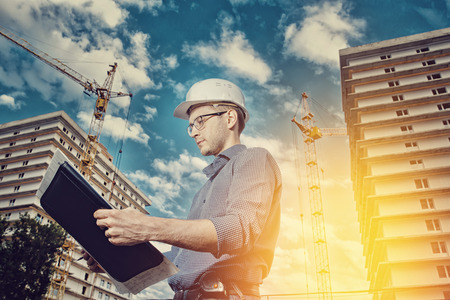 storey: Close-up man builder European wearing helmet, glasses, shirt in his hands holding folder, papers, blueprints background construction site: crane, multi-storey house.