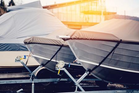 Rangée de bateaux entreposés pour l'hiver sous l'auvent. Entrepôt sur le quai de bateau. Préparation du concept pour l'hiver. Banque d'images - 81947707