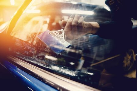 Il master installa una pellicola di colore per il vetro dell'auto con un asciugacapelli e una spatola con riflessi di luce. Auto di tintura di concetto Archivio Fotografico - 81947756