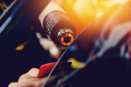 Il master installa una pellicola di colore per il vetro dell'auto con un asciugacapelli e una spatola con riflessi di luce. Auto di tintura di concetto Archivio Fotografico - 81947776