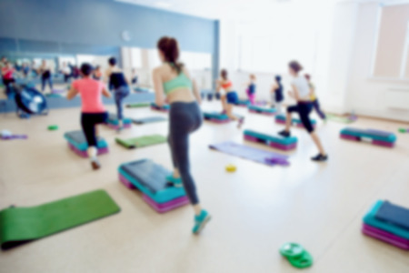 Blurred background of people group of girls playing in yoga and fitness,crossfit in the gym. Imagens