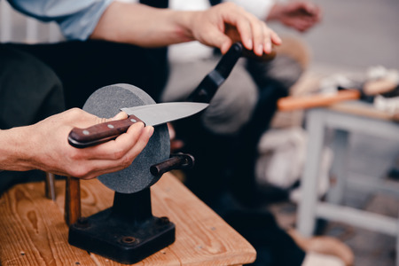 heavy: master sharpens the knife by tradition on a hand grindstone. Concept is an old craft, with your own hands. Stock Photo