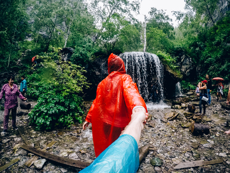 mountain Altai, RUSSIA - July 16, 2017: girl in a raincoat in the rain leads the guy to the waterfall.