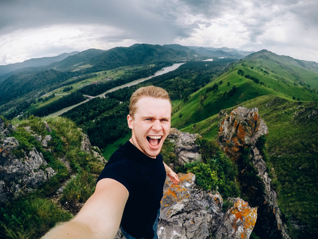 tourist man holds an action camera and takes pictures of himself against the background of mountains, forests, Gorny Altai, Russia. concept makes selfie Imagens
