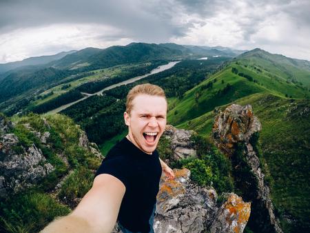 Touristenmann hält eine Aktionskamera und fotografiert sich vor dem Hintergrund von Bergen, Wäldern, Gorny Altai, Russland. Konzept macht Selfie