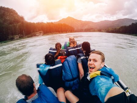 tourist man sitting in a boat and happy, a boat with a motor rides at high speed along the river. Concept rafting Stock Photo