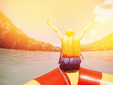 man sits on the edge of a rafting boat in rescued jelly and a protective helmet, rejoices, raises his hands up, rear view. Concept of active summer. Stock Photo