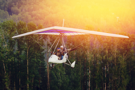 paraglider with pilot and passenger flies against background of forest and sunset, sunlight. concept is active extreme rest in open space. Stok Fotoğraf