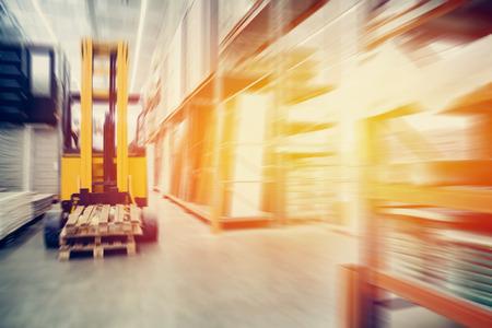 Entrepôt des locaux industriels pour le stockage des matériaux et du bois, il y a un chariot élévateur pour les conteneurs. Concept logistique, transport. Effet de flou de mouvement. Lumière du soleil éblouissante.