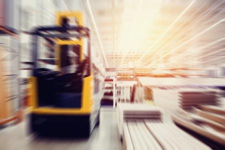 Almacén de locales industriales para almacenar materiales y madera, hay un montacargas para contenedores. Concepto de logística, transporte. Efecto de desenfoque de movimiento. Luz solar brillante. Foto de archivo
