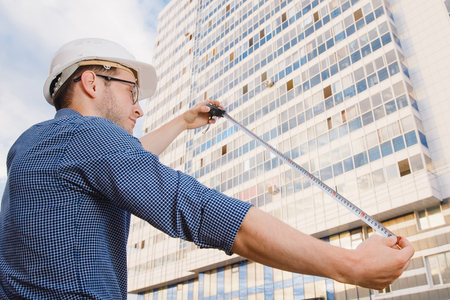 residential area: Male construction builder worker - foreman is an engineer in a protective helmet, glasses on the background of building a house with a crane Ruler measures. Concept calculation of construction time and cost. Stock Photo