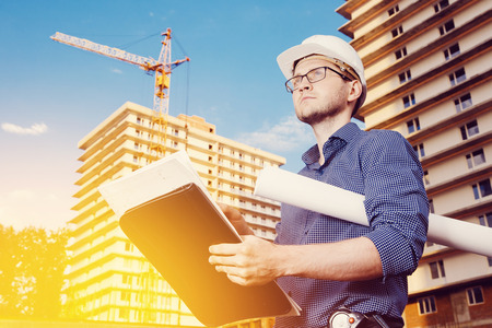 Close-up of a male construction worker wearing a helmet, glasses, a shirt in his hands holding a folder, papers, blueprints on the background of construction site: a crane, a multi-storey building.