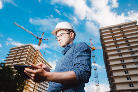 builder is a man in a protective helmet, glasses and a tablet computer in the hands of a crane, a multi-storey house and a blue sky. Concept construction, business, technology