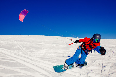 parachute jump: Snowboarder with a kite on fresh snow in the winter in the tundra of Russia against a clear blue sky. Teriberka, Kola Peninsula, Russia. Concept of winter sports snowkite.