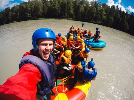 mountain Altai, biryuzovaya katun, RUSSIA - July 16, 2017: man in a helmet holds an action camera and makes selfie on the background of friends with oars, rafting