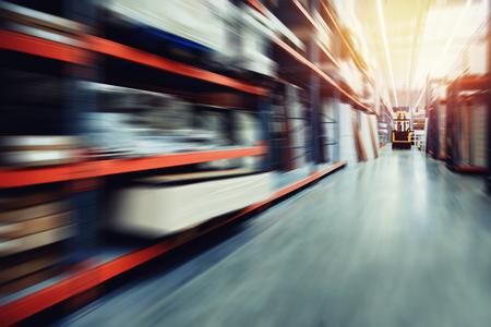 자재 및 목재 보관을위한 창고 산업 건물에는 컨테이너 용 지게차가 있습니다. 개념 물류, 전송입니다. 동작 흐림 효과. 밝은 햇빛.