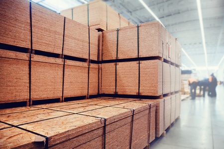 Warehouse industrial premises for storing materials and wood. Concept logistics, transport. Motion blur effect. Bright sunlight.