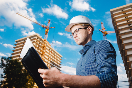 close-up man construction builder worker - foreman is engineer in protective helmet, glasses on the background of building house with crane. Concept calculation construction time, cost. Stock Photo