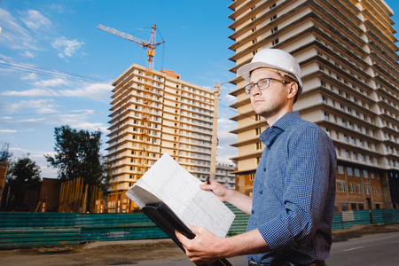 Close-up man builder European wearing helmet, glasses, shirt in his hands holding folder, papers, blueprints background construction site: crane, multi-storey house. Concept: construction, business.
