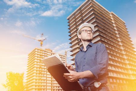 Close-up man builder European wearing helmet, glasses, shirt in his hands holding folder, papers, blueprints background construction site: crane, multi-storey house. Looks construction site