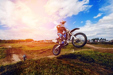マウンテン バイクのレーサーはモトクロスのレースに参加して、脱ぐし、参加者の背景の springboard でジャンプします。クローズ アップ。極端な残 写真素材