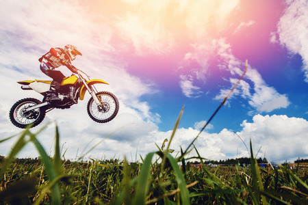 El piloto de una motocicleta participa en un motocross en vuelo, salta y despega en un trampolín contra el cielo. Concepto descanso extremo activo. rayo de luz