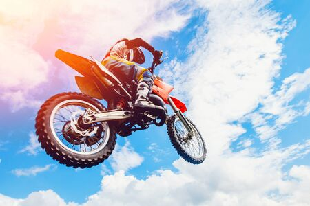road bike: racer on a motorcycle participates in motocross in flight, jumps and takes off on a springboard against the sky. Concept active extreme rest.