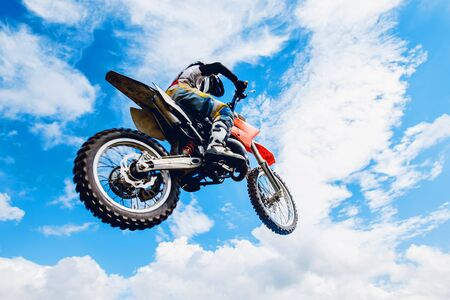 road bike: racer on a motorcycle participates in motocross cross-country in flight, jumps and takes off on a springboard against the sky. Concept active extreme rest.