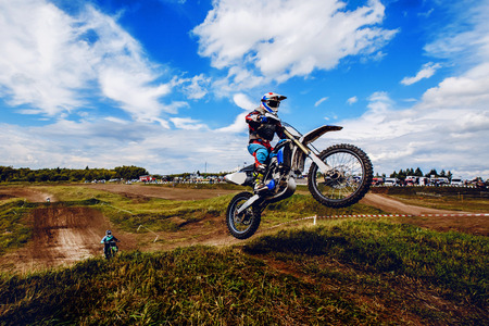 racer on mountain bike participates in motocross race, takes off and jumps on springboard, against the background of the participants. Close-up. concept of extreme rest, sports racing.