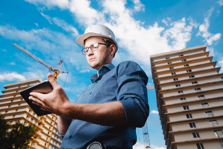 storey: builder is a man in a protective helmet, glasses and a tablet computer in the hands amid a crane, a multi-storey building outside, on the street. Concept construction, business, technology