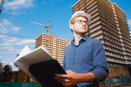 Close-up man builder European wearing helmet, glasses, shirt in his hands holding folder, papers, blueprints background construction site: crane, multi-storey house. Concept: construction, business.