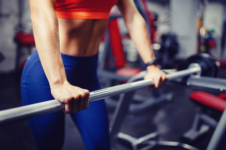 Close-up of a girl holding her hands with a barbell for pulling, squatting, fitness in the gym. Concept sports, toned picture, copyspace for text