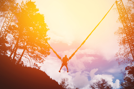 difficult lives: Man jumping on a rope up on a slingshot device. High contrast, silhouette of a man. Shine of the sun.
