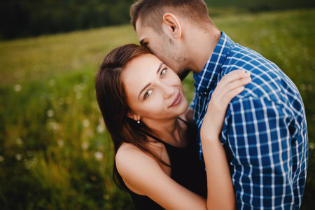 guy whispers his girlfriend in the ear compliments, words about love and tenderness. Concept lovers, a declaration of love, first love and a date. Stock Photo