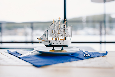 miniature sailing ship made of wood stands on a plate in a restaurant, behind it there is a window on the sea.