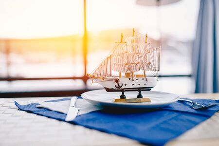 miniature sailing ship made of wood stands in a plate in the restaurant, behind it there is a window on the sea. Concept interior surroundings. Stock Photo