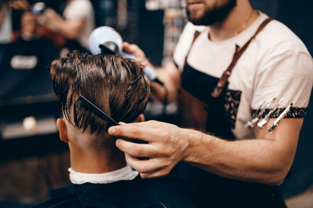 Close-up of a young hipster guy in a barbershop hairdresser cutting hair with scissors and a typewriter, waxing hair, blow-drying. Concept mens place, toned photo. Soft focus. Stock Photo