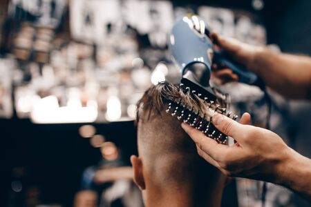 barbershop: Close-up of a young hipster guy in a barbershop hairdresser cutting hair with scissors and a typewriter, waxing hair, blow-drying. Concept mens place, toned photo. Soft focus. Stock Photo