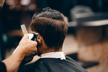 이발소에 남성 히피 고객 유행이 발, 후면보기에 미용사. 그들은 머리를 자르고, 헤어 드라이어와 왁스를 넣습니다. 헤어 케어의 개념입니다. 사진 톤.