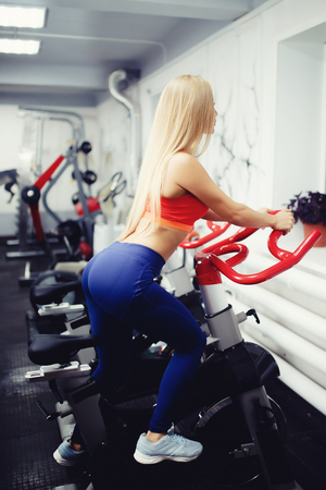 Girl blond European appearance of a sporty physique on a bike exercise simulator in a gym, view from behind to the buttocks. The concept of doing sports, maintaining a form, advertising a sports hall. Stock Photo
