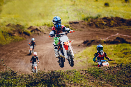 Young child racer on a motorcycle participates in motocross in flight, jumps and takes off on a springboard on the team of rivals. Concept active extreme rest.