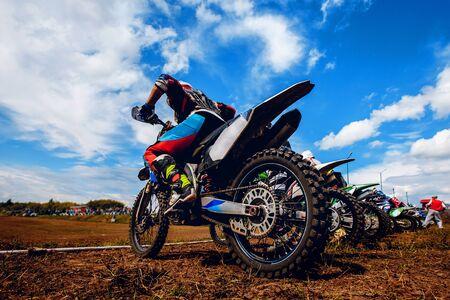 Racer op een motorfiets neemt deel aan motorcross voorbereiden op de start tegen een team van rivalen. Concept actieve extreme rust.