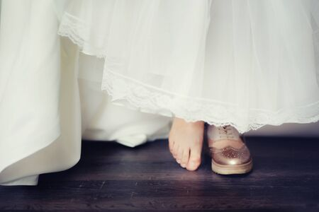 background blur bride in comfortable wedding shoes sneakers, the concept of choosing shoes shoes or sneakers or barefoot. Stock Photo
