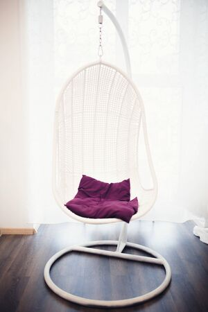 wicker chair chair hangs on chains in a white cafe room, a restaurant, a shop with white walls, a red purple pillow.
