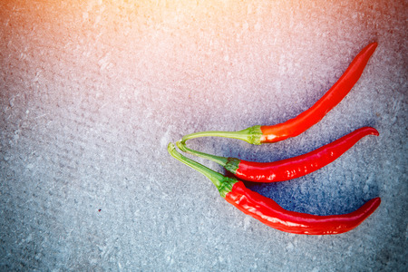 Close-up of chili pepper on a gray background. The concept is scalding, spicy, spicy. Blick light. Stock Photo