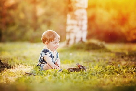 Little child boy rejoices rabbit against sunset background, warm light, glare from sun and light. Concept gift for the day of birth.