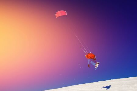 kiter: Snowboarder with a kite on fresh snow in the winter in the tundra of Russia against a clear blue sky. Teriberka, Kola Peninsula, Russia. Concept of winter sports snowkite.