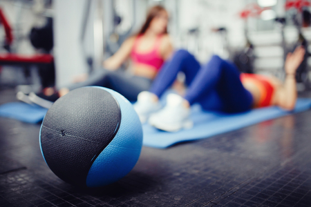Close-up of a medical ball on the background of people who are engaged in fitness in the gym. copyspace Stock Photo