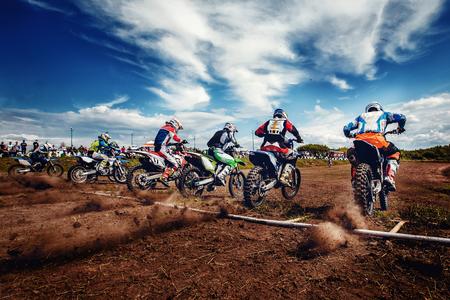 Team van atleten op mountainbikes begint, rook en stof vliegen van onder de wielen in het veld. Concept actieve rust motocross.